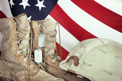 Old combat boots, dog tags, and helmet with American flag. In the background, closeup Stock Image