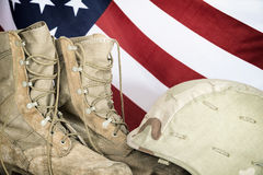 Old combat boots and helmet with American flag. In the background Royalty Free Stock Photography
