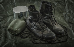 Old combat boots and military canteen Stock Image