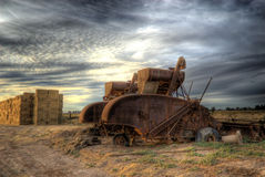 Old Combine Tractor. Old farm equipment rusts away on the side of the field under a dark sky of clouds Royalty Free Stock Photo