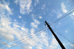 Old communications pole. Pole with many cables on a blue sky Stock Photography