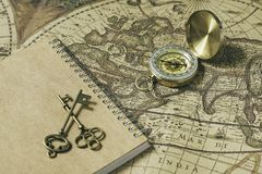 Compass, antique keys and notebook on blur vintage world map, journey concept, copy space. Old compass, antique keys and notebook on blur vintage world map Stock Photography
