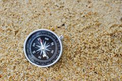 Old compass on beach. An old style compass pointing west resting on a sandy beach Royalty Free Stock Photo