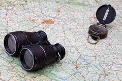Old compass and binoculars on map Stock Images
