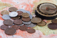 Old compass and coins on the map Royalty Free Stock Image
