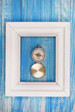 Old Compass in Photo frame on blue background Royalty Free Stock Images