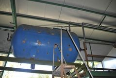 Old compressed air tank. Blue old compressed air tank suspended stock photos
