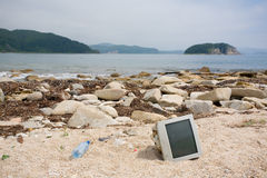 Old Computer Monitors, Bottles On The Beach. Royalty Free Stock Image