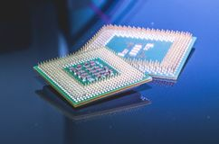 Old computer processors, CPU. Old CPUs on a glossy surface, both AMD and Intel processors stock photo