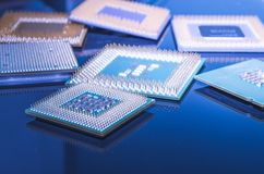 Old computer processors, CPU. Old CPUs on a glossy surface, both AMD and Intel processors stock images