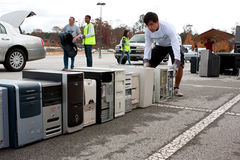 Old Computers Are Stacked At Recycling Day Event. Lawrenceville, GA, USA - November 23, 2013: A teen volunteer stacks a computer hard drive with other computer royalty free stock photography
