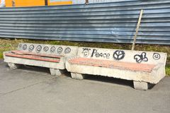 Old, concrete benches with pictures drawn by hooligans, in a city park.  stock photography