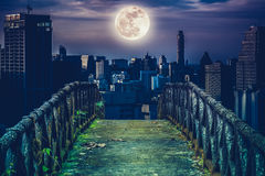 Old concrete bridge across to skyscrapers with super moon background. Cross process style. Old concrete bridge with wooden across to skyscrapers with super moon stock image