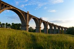Old concrete bridge in a wooded area. On a summer evening stock photo