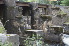 Old Concrete Dam. An old concrete dam shows its age with cracks discoloration and moss growing on it Stock Photography