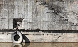 Old concrete mooring wall with automotive tire Stock Photo