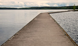 Old concrete pier on calm lake in Finland Royalty Free Stock Image