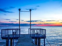 Old concrete pier with chains. Sunset red blue sky royalty free stock images