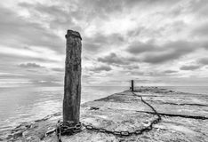 Old concrete pier with rusty chained poles Stock Photography