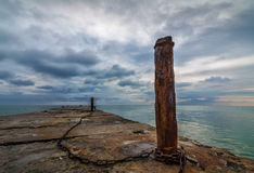Old concrete pier with rusty chained poles royalty free stock photo