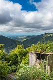 Old concrete structure with beautiful Puerto Rican valley in the. Background.  Cloudy sky and breakthrough sun on the foreground Royalty Free Stock Photos