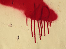 Old concrete wall with red paint runs. Close-up of old concrete wall with a spot of red spray paint resembling blood runs Royalty Free Stock Photography