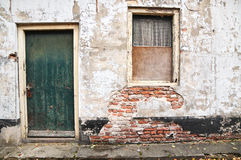 Old condemned house with green door. A very old, condemned house with green door with paint and plaster blistering off everywhere Stock Image