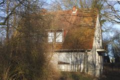 Old condemned residential  house. In winter with plants Royalty Free Stock Photo