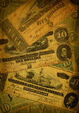 Old Confederate Money Background. Collage of old, dirty and very worn five, ten and dollar bills printed by the Confederate states of America in 1864 during the Stock Images