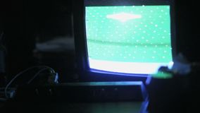 Old console in front of monitor screen. Close up of retro game console in front of old monitor with hipster arcade game playing stock video footage