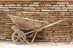 Old Construction cart on brick wall background Stock Image