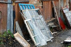 Old window frames and broken glass with boards in a heap of rubbish in the street. Old construction debris from window frames and broken glass on the street near royalty free stock photography