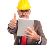 Old construction engineer reading good news on his tablet pad Stock Photo