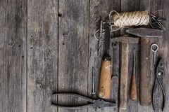 Old construction tools hammer, pliers, screwdriver, chisel lie on aged wooden boards of dark color with expressive texture.  stock photography