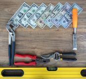Old construction tools and a set of dollar bills on a wooden table close-up stock image
