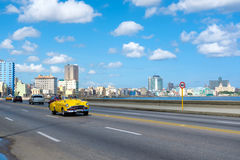 Old convertible car on the Havana malecon avenue. HAVANA,CUBA - JULY 14,2016 : Street scene with old convertible car on the Havana malecon avenue with a view of Royalty Free Stock Photography