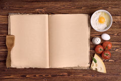 Old cook book, the ingredients for a meal on a background of wood Stock Photo