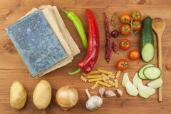 Old cookbook recipes on a wooden table. Cook healthy vegetable. Preparation of home diet food. Royalty Free Stock Image