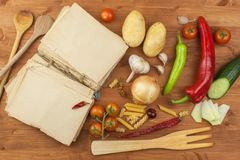 Old cookbook recipes on a wooden table. Cook healthy vegetable. Preparation of home diet food. Royalty Free Stock Images