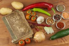 Old cookbook recipes on a wooden table. Cook healthy vegetable. Preparation of home diet food. Stock Photos