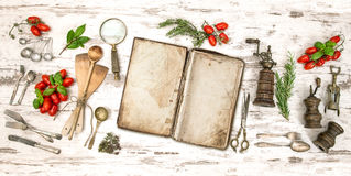 Old cookbook with vegetables, herbs and vintage kitchen utensils. Retro style toned picture Royalty Free Stock Image