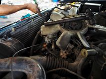 Old cooling fan motor of car is being removed in garage. Auto repair service. Old cooling fan motor of car is being removed in garage. Auto repair service Royalty Free Stock Photos