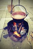 Old copper cauldron with fire made from logs. And antique effect royalty free stock photos