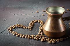 Old copper coffee pot and beans on dark rustic background. Old copper coffee pot and coffee beans in heart shape on dark rustic background Royalty Free Stock Image