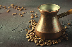Old copper coffee pot and beans on dark rustic background. Old copper coffee pot and coffee beans on dark rustic background, horizontal Stock Photography