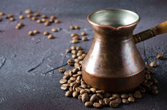Old copper coffee pot and beans on dark rustic background. Old copper coffee pot and coffee beans on dark rustic background, horizontal Royalty Free Stock Photos