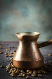 Old copper coffee pot and beans on dark rustic background. Old copper coffee pot and coffee beans on dark rustic background, vertical Royalty Free Stock Images