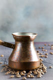 Old copper coffee pot and beans on dark rustic background. Old copper coffee pot and coffee beans on dark rustic background, vertical Stock Images