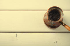 Old copper coffee pot on white wooden background Royalty Free Stock Images