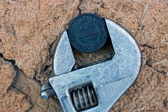 Old copper coin sandwiched in a wrench on dry clay stock images